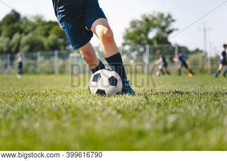 Junior Level Football Player Kicking Ball. Legs Of Soccer Striker Playing Training Game. Closeup Ima