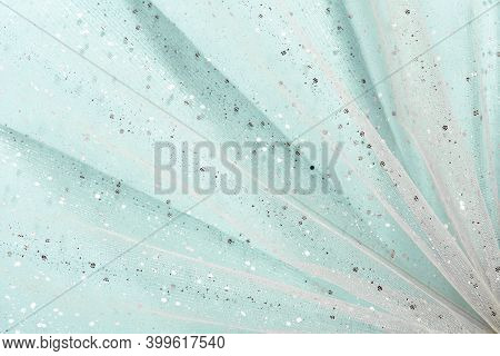 Draped Fabric Waves With Silver Glitter On Light Blue Background. Abstract, Chic Holiday Flat Lay.