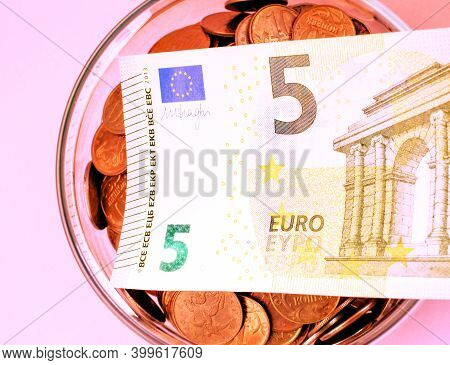 5 Euro Lies In A Glass Jar With Metal Coins Isolated On A Light Background. Store And Protect Saving