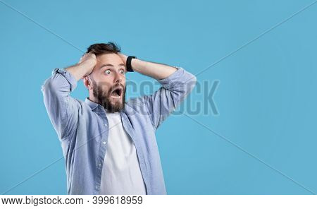 Shocked Millennial Guy Shouting And Holding His Head In Disbelief, Looking At Empty Space On Blue St