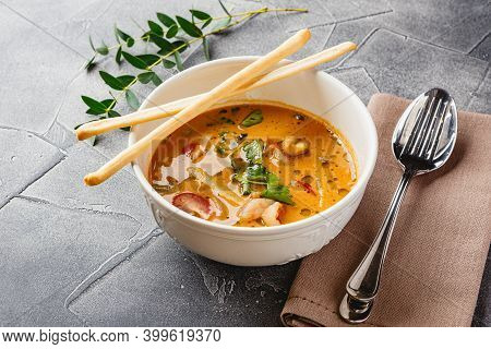 Tom Yam Kung Thai Soup With Shrimp, Seafood, Coconut Milk And Chili Pepper In White Bowl