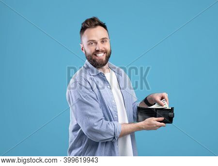 Cool Bearded Guy Holding Wallet Full Of Money Over Blue Studio Background. Wealthy Millennial Man Sh