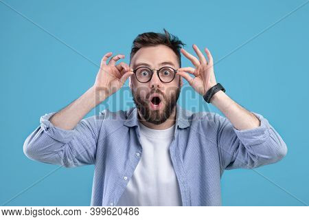 Shocked Young Guy In Casual Wear And Glasses Opening Mouth In Surprise On Blue Studio Background. At