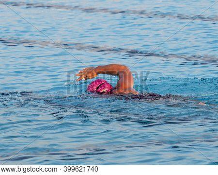A Female Wearing A Pink Swim Cap Swimming In A Pool Alone.