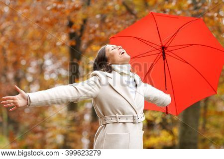 Happy Fashion Adult Woman With Umbrella Celebrating Autumn Stretching Arms In A Park