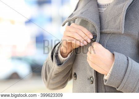 Close Up Of A Woman Hands Fastening Button Of Jacket In Winter In The Street