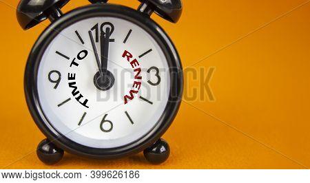 Time To Renew Symbol. Beautiful Black Alarm Clock With Words 'time To Renew'. Beautiful Orange Backg