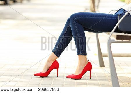 Side View Portrait Of A Beauty Woman Legs With Jeans And High Heels Sitting In A Bench