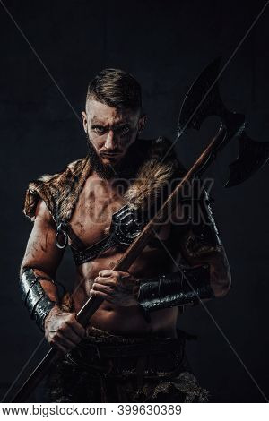 Dressed In Dark Armour With Fur Dirty And Awesome Viking Fighter With Two Handed Axe On His Shoulder