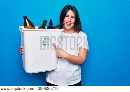 Young beautiful woman recycling glass bottles on wastebasket to care environment smiling happy pointing with hand and finger