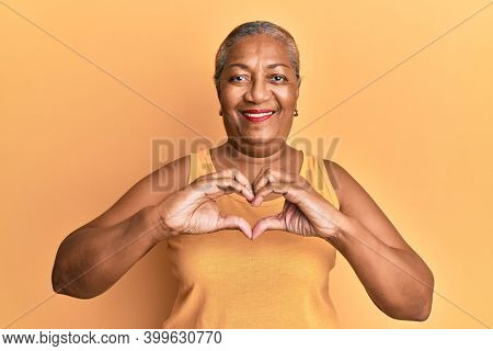 Senior african american woman wearing casual style with sleeveless shirt smiling in love doing heart symbol shape with hands. romantic concept.