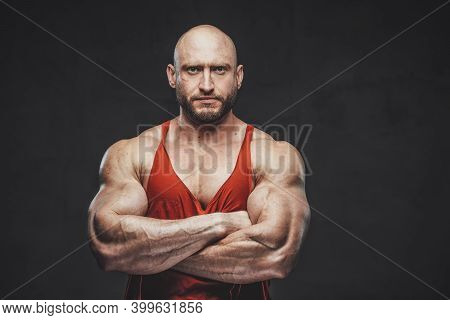 Powerful And Hairless Guy In Red Shirt With Beard And Strong Hands Poses In Dark Background Looking