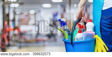 The Concept Of Cleaning The Fitness Room. Cleaning Lady With A Bucket Of Cleaning Products Stands Ag