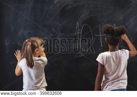 Two Beautiful Little Girls Solving Math Problems On A Chalkboard In Classroom While On Math Lesson