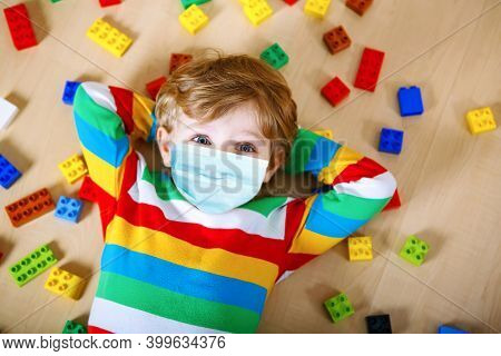 Little Blond Child Playing With Lots Of Colorful Plastic Blocks Indoor. Little Toddler Boy In Medica
