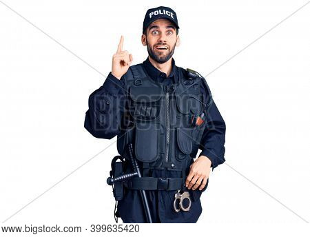 Young handsome man with beard wearing police uniform pointing finger up with successful idea. exited and happy. number one.