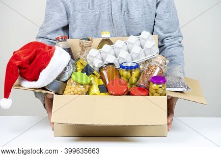Christmas Donation. Volunteer Holding Food Donation Box With Grocery Products