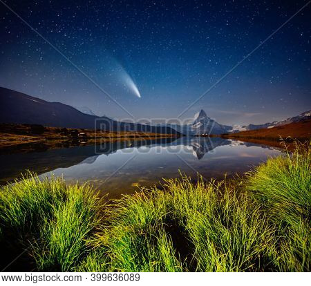 Famous Matterhorn spire under the starry sky. Location Stellisee lake, Cervino peak, Swiss alp, Switzerland, Europe. Image of popular touristic place. Long exposure shot. Discover the beauty of earth.