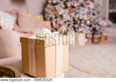 Presents And Gift Boxes Under Christmas Tree. Beige Boxes With Ribbon Bow. New Year Decorated House