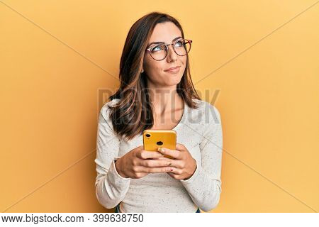 Young brunette woman using smartphone over yellow background smiling looking to the side and staring away thinking.