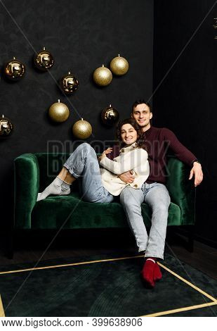 Couple In Love Sits On The Sofa Around The Room Is Decorated With Christmas Decor. Christmas Decor A
