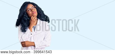 Beautiful african american optician woman with optometry glasses serious face thinking about question with hand on chin, thoughtful about confusing idea