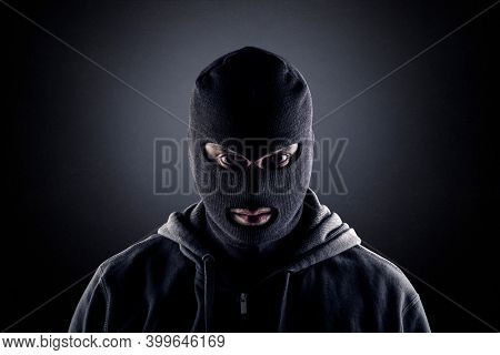 Criminal wearing black balaclava and hoodie in the dark