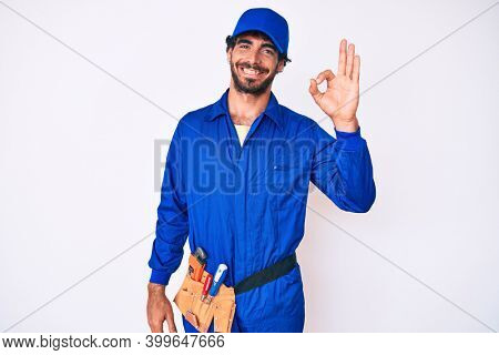 Handsome young man with curly hair and bear weaing handyman uniform smiling positive doing ok sign with hand and fingers. successful expression.