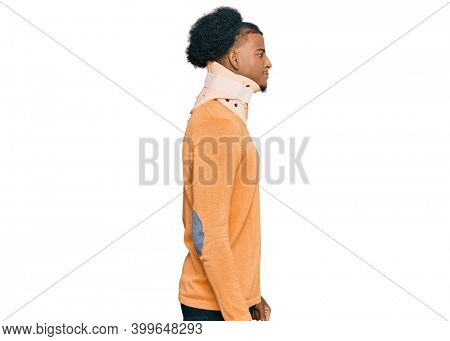 African american man with afro hair wearing cervical neck collar looking to side, relax profile pose with natural face with confident smile.