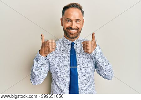 Handsome middle age man wearing business shirt and tie success sign doing positive gesture with hand, thumbs up smiling and happy. cheerful expression and winner gesture.