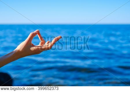 Unrecognizable person gesturing Gyan mudra and meditating near rippling blue sea on summer day on resort