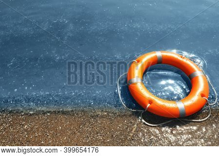 Orange Life Buoy On Sand Near Sea. Emergency Rescue Equipment