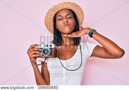Young african american woman wearing summer hat holding vintage camera cutting throat with hand as knife, threaten aggression with furious violence