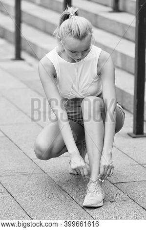 Keep Foot Locked In Place. Sporty Woman Tying Shoelaces. Athletic Woman In Sportswear Training On St