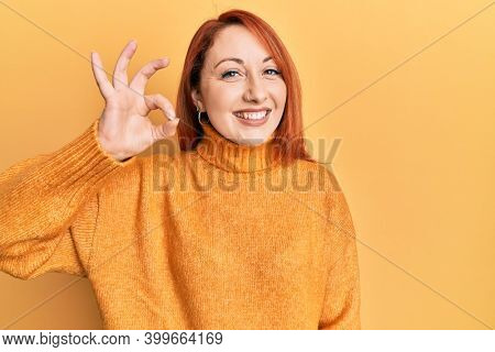 Beautiful redhead woman wearing casual winter sweater over yellow background smiling positive doing ok sign with hand and fingers. successful expression.