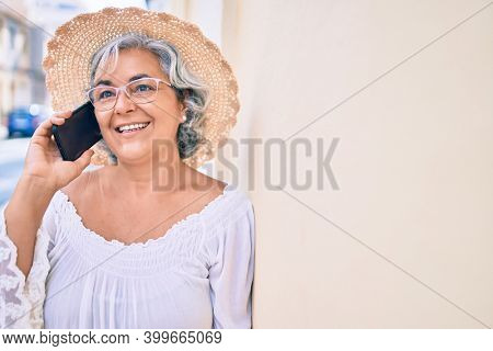 Middle age woman with grey hair smiling happy outdoors speaking on the phone
