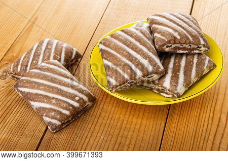 Gingerbread On Wooden Table, Few Striped Gingerbreads In Yellow Glass Saucer
