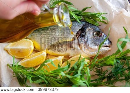 Dorada With Lemon And Fresh Herbs, The Chef Pours Oil On The Fish Before Baking