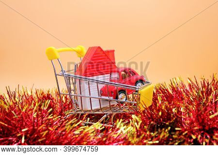 Russia, Vladivostok, October 17, 2020: A Toy House And A Red Toy Car In A Small Shopping Cart . Majo
