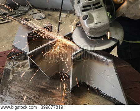 Worker Grinds Metal Part With Angle Grinder And Produces Lot Of Sparks