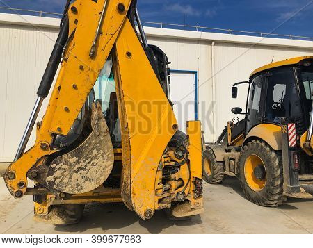 Parked Yellow Backhoe Loader. Earthmoving, Excavating, Digging Machinery At Construction Site