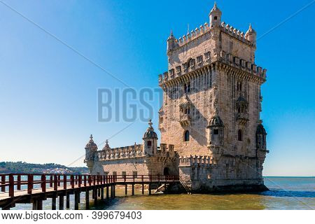 Scenic Belem Tower And Wooden Bridge Miroring With Low Tides On Tagus River. Torre De Belem Is Unesc