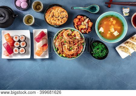 Japanese Food Banner With Copy Space. Sushi, Miso Soup, Udon, Tea Etc, Overhead Shot On A Blue Backg