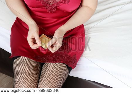 Woman Opening Condom On The Bed, Contraception, Safe Sex Concept. Girl In Black Fishnet Stockings An