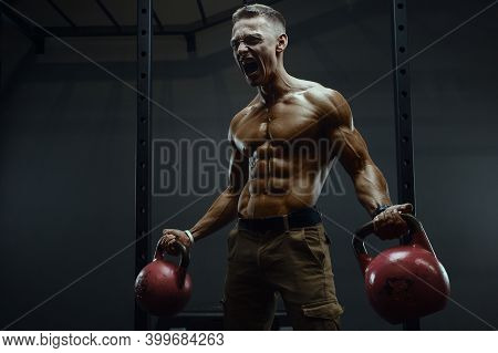 Fitness Man Pumping Up Muscles With Kettlebell