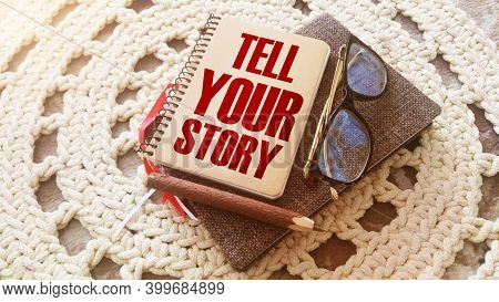 Text Tell Your Story On The Cover Of Book, Glasses And Pen. Business Concept For Storytelling Tellin