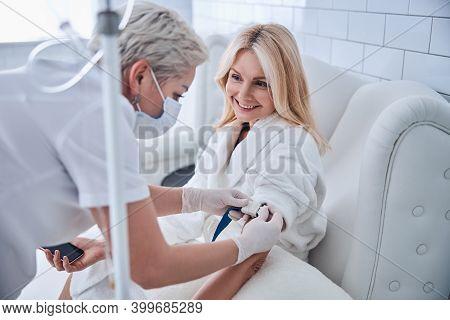 Pretty Caucasian Woman In White Bathrobe Sitting In Cosmetic Armchair In Beauty Clinic