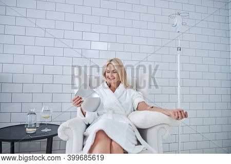 Happy Smiling Female Receiving Intravenous Vitamin Therapy In Beauty Clinic