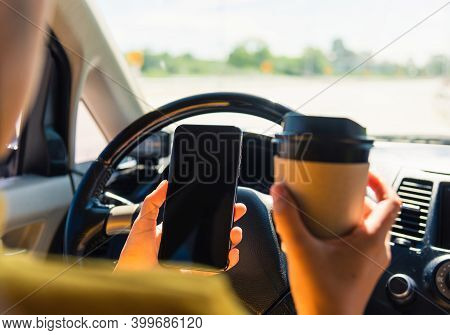 Asian Woman Drinking Hot Coffee Takeaway Cup Inside A Car And Using Smartphone Blank Screen While Dr