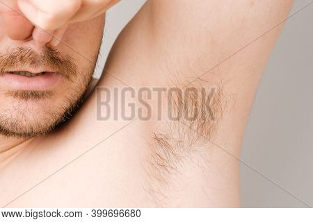 Close Up Of Man Armpit With Long Unshaved Hair And Pinching Nose From Sweaty Bad Smell